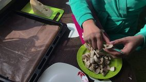 Een vrouw snijdt champignons op een scherpe raad De kaas ligt op een plaat naast het stock videobeelden