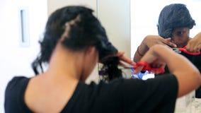 Een vrouw snijdt haar haar af stock footage