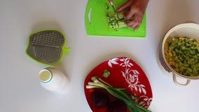 Een vrouw snijdt een komkommer op een scherpe raad Naast de plaat zijn andere ingrediënten voor groentesoep gekookte bieten en on stock footage