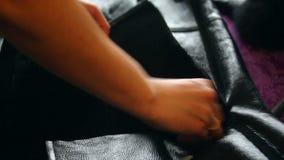 Een vrouw snijdt schapehuidlagen om een kap te maken Snijdt de vloer af, verwijdert wol uit de besnoeiing stock footage