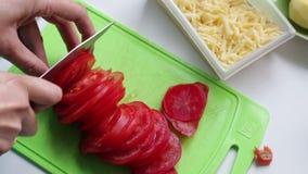 Een vrouw snijdt een tomaat op een scherpe raad Daarna, gehakte kaas en aardappels stock video