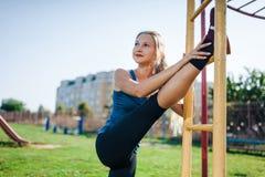 Een vrouw in sportkleding die opwarmingsoefeningen doen Stad in zonnige avond De geschikte geschiktheidsvrouw die het uitrekken d stock foto