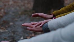 Een vrouw strijkt zacht een man hand Zij zitten romantically door de brand en verwarmen zich stock videobeelden