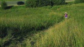 Een vrouw in een strohoed beklimt een berg langs de weg Het schieten vanaf de bovenkant stock footage