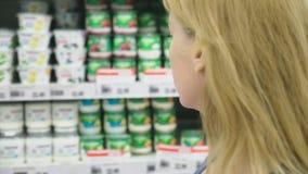Een vrouw in een supermarkt gaat door de mand voorbij de tellers over 4k, close-up stock footage
