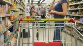 Een vrouw in een supermarkt gaat door de mand voorbij de tellers over 4k, close-up, loopt een vrouw rond de supermarkt stock videobeelden