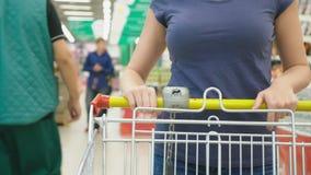 Een vrouw in een supermarkt gaat door de mand voorbij de tellers over 4k, close-up, loopt een vrouw rond de supermarkt stock video