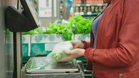 Een vrouw in supermarkt het kopen groenten komkommers en tomaten, die op schalen wegen Zelfbediening 4K stock videobeelden