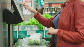 Een vrouw in supermarkt het kopen groenten komkommers en tomaten, die op schalen wegen Zelfbediening 4K stock video