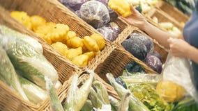 Een vrouw in supermarkt het kopen groenten, pompoen stock video