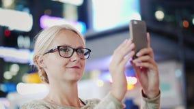 Een vrouw is een toerist in een grote stad Met bewondering met een smartphone wordt gefotografeerd die Times Square, New York stock video