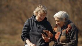 Een vrouw toont foto's op haar bejaarde moeder` s smartphone Een vrouw helpt haar bejaard moedergebruik haar smartphone stock footage