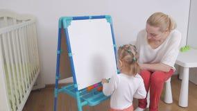 Een vrouw toont haar weinig dochter een tekenbord Het kind was gelukkige gift stock video