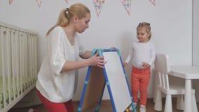 Een vrouw toont haar weinig dochter een tekenbord Het kind was gelukkige gift stock videobeelden