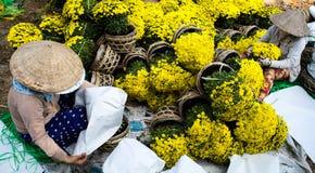 Een vrouw in traditionele kegelhoed, verpakkende en verkopende bloemen, Maannieuwjaar in Vietnam, A Stock Foto