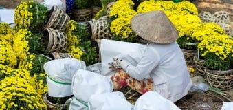 Een vrouw in traditionele kegelhoed, verpakkende en verkopende bloemen, Maannieuwjaar in Vietnam, A Stock Afbeeldingen