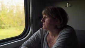 Een vrouw in een treinauto kijkt uit het venster stock videobeelden