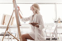 Een vrouw trekt een beeld op de schildersezel Stock Foto's