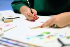 Een vrouw trekt een kleurpotlood op papier stock afbeelding