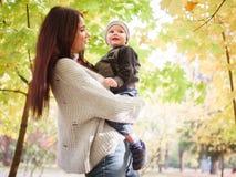 Een vrouw, tribunes in de herfst parkeert en houdt op handen bekijkend haar weinig zoon Het Concept de Familie royalty-vrije stock afbeelding