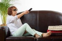 Een vrouw van rijpe TV van het leeftijdshorloge Stock Fotografie