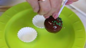 Een vrouw verfraait met decoratieve vulling een spatie van de cake pop cake De vullingsstokken aan de gesmolten chocolade stock videobeelden