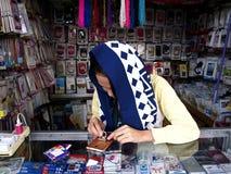 Een vrouw verkoopt een grote verscheidenheid van smartphone en toebehoren in haar opslag Royalty-vrije Stock Foto