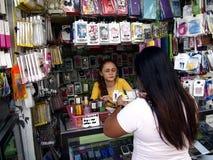 Een vrouw verkoopt een grote verscheidenheid van smartphone en toebehoren in haar opslag Royalty-vrije Stock Foto's