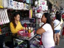 Een vrouw verkoopt een grote verscheidenheid van smartphone en toebehoren in haar opslag Stock Afbeeldingen