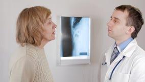 Een vrouw verouderde bij een artsen` s ontvangst Hoest en besprekingen over gezondheidsproblemen De man spreekt de diagnose stock videobeelden