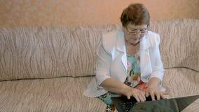 Een vrouw verouderde, thuis werkend aan laptop stock videobeelden