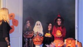 Een vrouw verspreidt suikergoed aan kinderen voor Halloween stock video