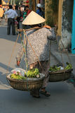 Een vrouw vervoert bananen in manden in een straat van Hoi An (Vietnam) Stock Afbeelding