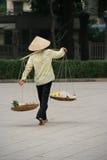 Een vrouw vervoert goederen in manden in een straat van Hanoi (Vietnam) Stock Fotografie