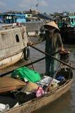 Een vrouw vervoert goederen op een roeiboot (Vietnam) Stock Foto's