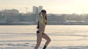 Een vrouw verwijdert haar hoed terwijl het lopen in een zwempak in de winter stock videobeelden