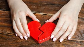 Een vrouw verzamelt een gebroken hart in zijn handen Concept liefde en verhoudingen Familiepsychotherapist de diensten verzoening royalty-vrije stock fotografie
