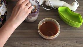 Een vrouw voegt honing aan grondpinda's en zonnebloemzaden toe om halva te maken Naast de container is honing om aan de mengeling stock video