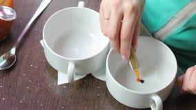 Een vrouw voegt voedselkleuren aan een verschillende kop toe Voor de voorbereiding van gekleurde room stock video