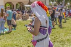 Een vrouw in een volledig kostuum van de lichaamseenhoorn verzendt een tekst tijdens trots stock foto's
