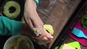 Een vrouw vormt ringen van fijngestampte aardappels op een bakselblad Met behulp van gebakjezak Naast andere ingrediënten voor he stock videobeelden