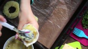 Een vrouw vormt ringen van fijngestampte aardappels op een bakselblad Met behulp van gebakjezak Naast andere ingrediënten voor he stock footage