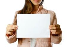 Een vrouw in een warm de winterjasje die een wit pamflet houden Leeg document Sluit omhoog Geïsoleerdj op witte achtergrond stock afbeeldingen