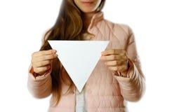 Een vrouw in een warm de winterjasje houdt een driehoekig wit pamflet Leeg document Sluit omhoog Geïsoleerdj op witte achtergrond royalty-vrije stock afbeeldingen