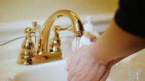 Een vrouw wast haar handen onder de kraan Loodgieterswerk en watervoorziening stock footage