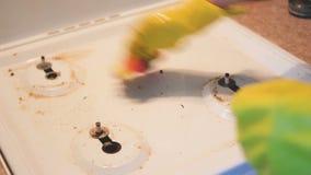 Een vrouw wast het fornuis Het fornuis wordt schoon stock videobeelden