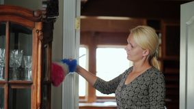 Een vrouw wast het stof van het buffet met de schotels Het schoonmaken van het huis stock video