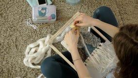 Een vrouw weeft op een weefgetouw een mooi die borduurwerk van garen, in een huisstudio wordt gemaakt, stock videobeelden