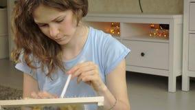 Een vrouw weeft op een weefgetouw een mooi die borduurwerk van garen, in een huisstudio wordt gemaakt, stock footage
