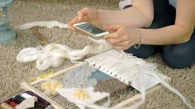 Een vrouw weeft op een weefgetouw een mooi die borduurwerk van garen wordt gemaakt, in een huisstudio, Foto's op de telefoon stock footage